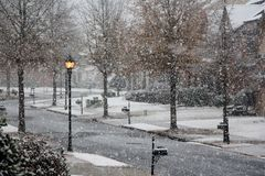 A snowing winter day on the street. A snowing winter day on suburban street during the day Stock Photos