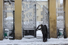 Snowing in winter. Unrecognizable people sheltering from wind and snow using umbrella in Zagreb, Croatia Royalty Free Stock Image