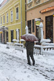 Snowing in winter. Zagreb, Croatia - December 28. Man sheltering from wind and snow under an umbrella in Zagreb, Croatia Royalty Free Stock Photos