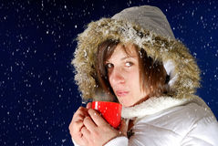 Snowing on young woman drinking something hot. Snowing on young woman in white winter coat drinking something hot Stock Photo