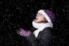 Snowing on young woman in winter clothes Stock Photos