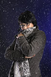 Snowing on young woman with wintercoat and shawl Royalty Free Stock Image