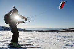 Snowkiting (kiteboarding) -运动员在滑雪滑动在日落 库存图片