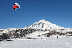 Snowkiting: sportsman glides on skis on background volcano Royalty Free Stock Image