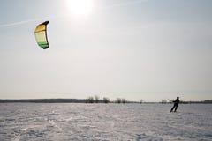 Snowkiting sur le champ sur un fond des arbres et du soleil Photos libres de droits