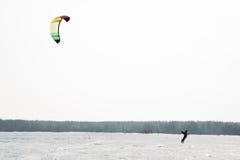 Snowkiting sur le champ sur un fond des arbres et du soleil Photo stock