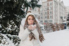 Snowlakes de soufflement de charme de fille joyeuse de ses mains dans le jour d'hiver extérieur sur la rue Jeune femme stupéfiant photographie stock