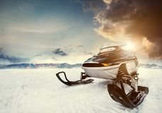 Snowmachine on the mountain lake frozen surface with thunderstorm clouds on the background Stock Images