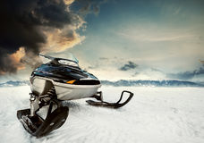 Snowmachine on the mountain lake frozen surface with thunderstorm clouds on the background Royalty Free Stock Photography