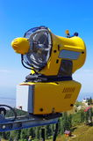 Snowmaking on blue background, in the summer. Yellow Snow cannon in Carpathian Mountains, Romania Stock Images