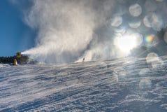 Snowmaking spraying snow on the piste for mountain skiers stock photo