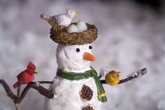 Snowman. A holiday figurine from a christmas setting. This statue is of a snowman with birds nesting on him stock image