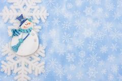 Snowman. A snowflake and a snowman on a blue snowflake background, Christmas Time Stock Photos