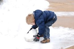 The snowman. A three year old boy starts to make a snowman Royalty Free Stock Photo