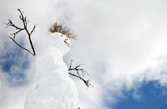 Snowman. A snowman with stick features against a cloudy blue sky Royalty Free Stock Images