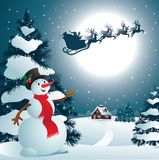 Snowman. Cute snowman on the background of night sky with a bright moon and the silhouette of Santa Claus flying on a sleigh pulled by reindeer Stock Photo