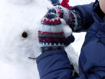 Snowman. Little boy making a snowman in the wintertime Stock Image