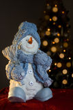 Snowman. Christmas ornament with blurred christmas tree lights in the background (shallow depth of field on Stock Images