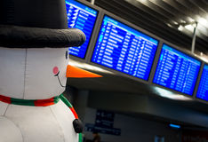 Snowman on the background of the schedule of flights to Moscow Vnukovo airport. Moscow, Russia - December 29, 2015: Snowman on the background of the schedule of stock photos