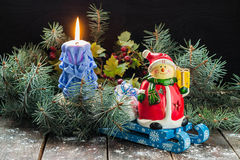 Snowman and bag with gifts on a sled, candle in the spruce branc Stock Images