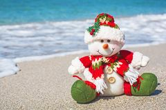 Snowman in red santa hat on beach in hat royalty free stock photography