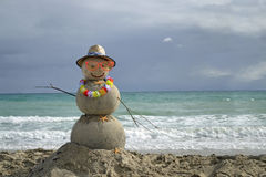 Snowman on beach. Winter vacation. Snowman made of sand on the beach with ocean background Royalty Free Stock Photography