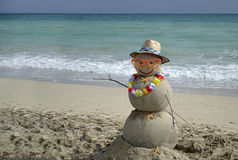Snowman on beach. Winter vacation. Snowman made of sand on the beach with ocean background Stock Photos