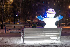 Snowman on the bench. Winter 2013-2014. January 23, 2014. Russia. Moscow. Bibirevo. Christmas decorations of the city park. Highlighted Snowman on a Park bench Royalty Free Stock Photos