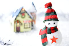 Snowman with black and red hat. And scarf in artificial snow on white background Royalty Free Stock Photo