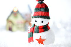 Snowman with black and red hat. And scarf in artificial snow on white background Royalty Free Stock Photos