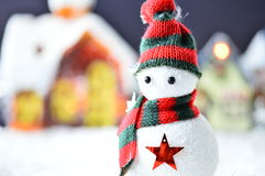 Snowman with black and red hat. And scarf in artificial snow on dark background Royalty Free Stock Photo