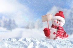 Snowman with a blank placard on the snow Stock Photos