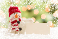 Snowman with Blank White Card Over Abstract Snow and LIght Stock Photography