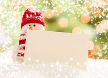 Snowman with Blank White Card Over Abstract Snow and LIght Royalty Free Stock Photos