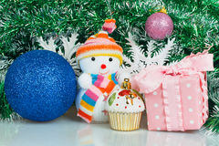 Snowman with blue ball, pink gift box and white snowflake Stock Photos
