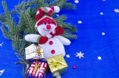 Snowman on a blue Christmas table cloth. Decorated with a fir branch and bunch of presents and stars Stock Image
