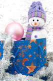 Snowman with blue gift box and pink bauble on a background of si Stock Photo