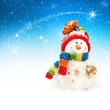 Snowman. On a blue sky background with falling snowflakes Stock Photo