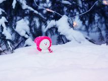 Card with a festive cute toy snowman in a bright pink cap sitting in a snowdrift with a gift under the Christmas tree in. Snowman in a bright pink cap sitting in stock photo