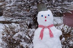 Snowman with a bucket on his head near the tree royalty free stock image