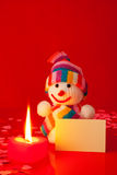 Snowman with burning heart shaped candle Stock Photos