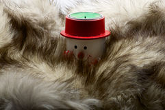 Snowman candle in fur. Snowman candle in scarf and red hat in furs royalty free stock photo