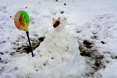 Snowman with a carrot in the yard of a house stock images