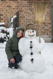 Snowman and child in the yard Stock Image