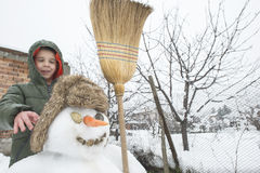 Snowman and child in the yard Stock Photography