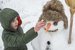 Snowman and child in the yard Royalty Free Stock Photo