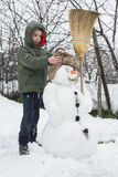 Snowman and child in the yard Stock Images