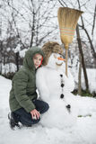 Snowman and child in the yard Royalty Free Stock Images
