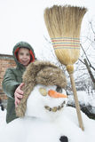 Snowman and child in the yard Royalty Free Stock Image