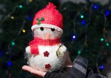 Snowman in children's hands. Snowman in red hat in children's hands Royalty Free Stock Photo